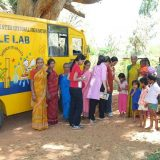 A group of standing in front of bus and giving books to the kids