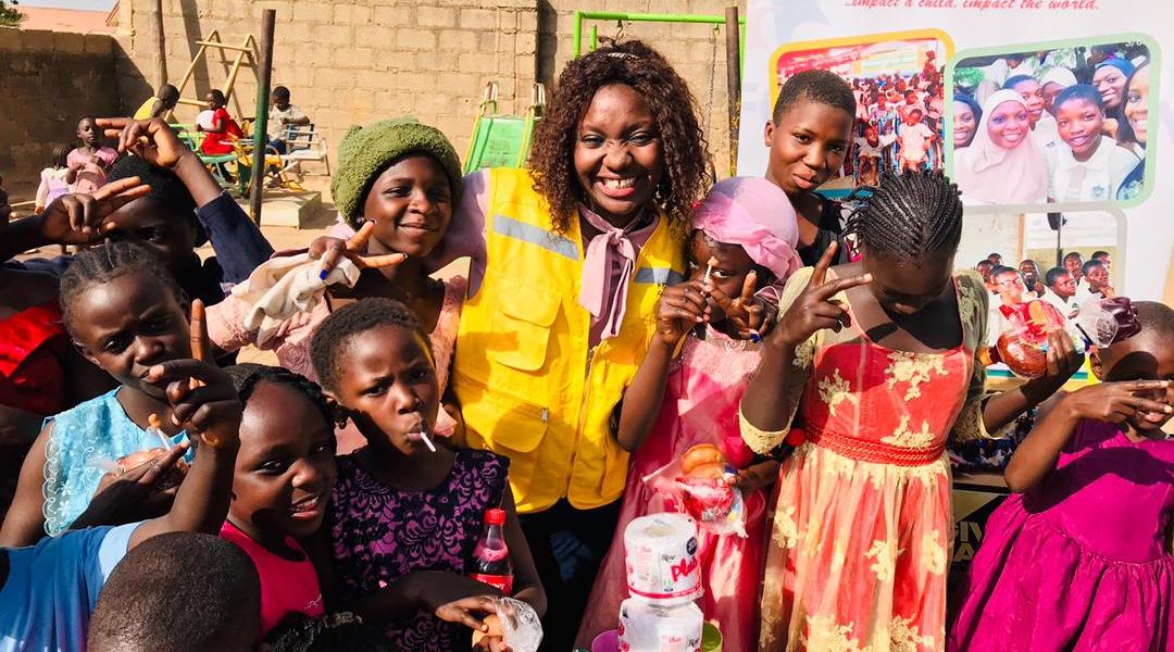 A woman standing with kids and smiling